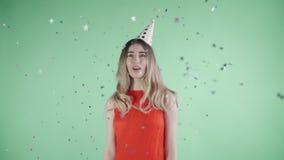 Красивая девушка в шляпе партии стоит под confetti на зеленой предпосылке сток-видео