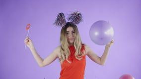 Красивая девушка в шляпе партии танцует под падая confetti и воздушными шарами на пурпурной предпосылке видеоматериал