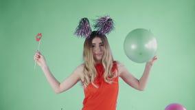 Красивая девушка в шляпе партии танцует под падая confetti и воздушными шарами на зеленой предпосылке видеоматериал