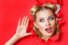 Красивая девушка в щелях из отверстия в красной бумаге, красивом ярком макияже, выражениях лица сюрприза и интересе стоковые фото