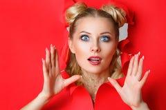 Красивая девушка в щелях из отверстия в красной бумаге, красивом ярком макияже, выражениях лица сюрприза и интересе стоковые изображения rf