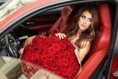 Красивая девушка в элегантном платье представляя в роскошном автомобиле с bo Стоковая Фотография RF