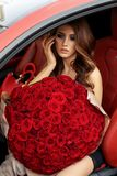 Красивая девушка в элегантном платье представляя в роскошном автомобиле с bo Стоковые Изображения RF