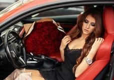 Красивая девушка в элегантном платье представляя в роскошном автомобиле с bo Стоковая Фотография