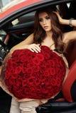 Красивая девушка в элегантном платье представляя в роскошном автомобиле с bo Стоковые Фото