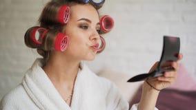 Красивая девушка в curlers, в утре после ванны красит ее губы сток-видео