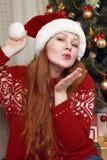 Красивая девушка девушки redhead делая поцелуй в украшении рождества Интерьер дома с елью и подарками Hol кануна Нового Годаа и з Стоковое Фото
