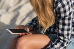 Красивая девушка держа smartphone в руках на пляже около песка берега моря на заднем плане Стоковые Изображения