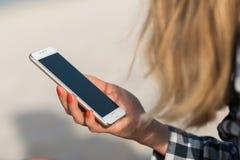 Красивая девушка держа smartphone в руках на пляже около песка берега моря на заднем плане Стоковые Изображения RF