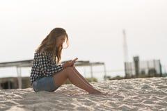 Красивая девушка держа smartphone в руках на пляже около песка берега моря на заднем плане Стоковое Изображение