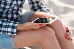 Красивая девушка держа smartphone в руках на пляже около песка берега моря на заднем плане Стоковая Фотография RF