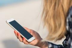 Красивая девушка держа smartphone в руках на пляже около песка берега моря на заднем плане Стоковое фото RF