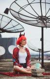 Красивая девушка дьявол сидит на крыше дома в ожидании хеллоуин Портрет на предпосылке большого Стоковое Фото