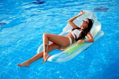 Красивая девушка загорая в бассейне на раздувном тюфяке стоковые фото
