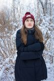 Красивая девушка замерзая в лесе зимы Стоковое Изображение RF