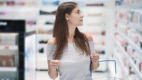 Красивая девушка идет к магазину косметик с корзиной, замедленным движением, снятым steadicam видеоматериал