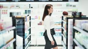 Красивая девушка идет среди полок в косметиках ходит по магазинам, замедленное движение, снятое steadicam видеоматериал