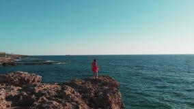 Красивая девушка идя на большие утесы Кавказское положение женщины на скалистом пляже Дама в красном платье поднимает оружия к ст сток-видео