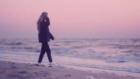 Красивая девушка идя на влажный песок seashore на восходе солнца сток-видео