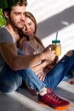 Красивая девушка и красивый бородатый парень сидят на поле стоковое изображение