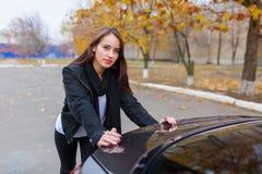 Красивая девушка и черный автомобиль стоковые фото