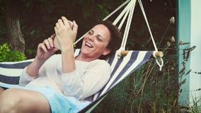 Красивая девушка лежит в гамаке и играет с ее smartphone