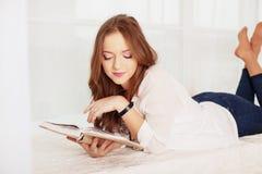 Красивая девушка лежит и читает книгу Концепция отдыха a Стоковое Изображение