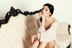 Красивая девушка лежит на софе в белье стоковое изображение rf