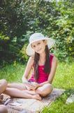 Красивая девушка 10 лет в белой шляпе сидя на траве в саде лета стоковое фото rf