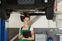 Красивая девушка механика в зеленых прозодеждах и серой футболке d стоковое изображение rf