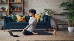 Красивая девушка наблюдает консультации йоги на экране компьтер-книжки и работает сидеть на поле дома самостоятельно самомоднейше сток-видео