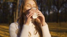 Красивая девушка наслаждаясь теплым напитком в лучах солнца осени, идя в парк сток-видео