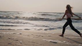 Красивая девушка, на пляже, на море летом, имеющ потеху, делая сальто, колесо видеоматериал