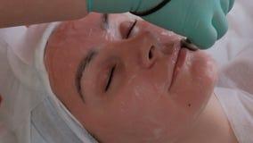 Красивая девушка на cosmetological процедуре в салоне красоты Руки beautician тратят электроды на кожа стороны видеоматериал