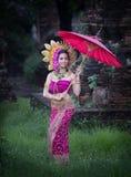 Красивая девушка нося тайское backg подачи цветка платья и зонтика Стоковое Изображение