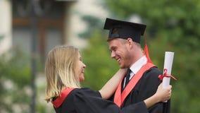 Красивая девушка обнимая и целуя ее парня, счастливые студент-выпускники наслаждаясь жизнью видеоматериал