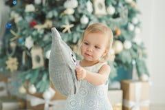 Красивая девушка около украшенной рождественской елки с лошадью игрушки деревянной тряся E Маленькая девочка портрета стоковая фотография