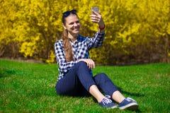 Красивая девушка ослабляет в парке и принимает selfie на зеленой траве около дерева в желтом цветении Стоковая Фотография RF