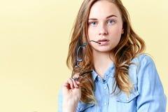Красивая девушка подростка при волосы, веснушки и голубые глазы имбиря держа стекла чтения, молодую женщину с зрелищами Стоковые Изображения RF