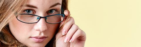 Красивая девушка подростка redhead при веснушки нося стекла чтения, усмехаясь предназначенный для подростков портрет Стоковое Изображение RF