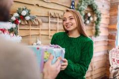Красивая девушка принимает подарок рождества от парня и улыбок indoors стоковое фото rf