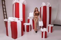 Красивая девушка при светлые волосы представляя с подарками на рождество Стоковая Фотография