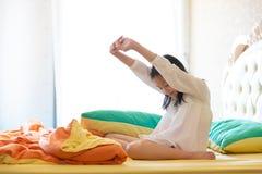 Красивая девушка просыпая вверх в ее кровати, азиатском усмехаться девушки и stret стоковая фотография