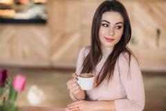 Красивая девушка распологая в кафе и выпивая капучино Стоковая Фотография RF