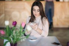 Красивая девушка распологая в кафе и выпивая капучино Стоковые Фотографии RF
