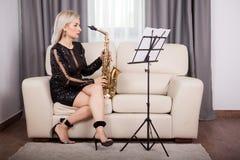 Красивая девушка саксофониста играя на ее музыкальном инструменте внутри Стоковое Изображение RF