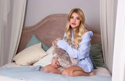 Красивая девушка сидит на кровати и объятия pillow Стоковая Фотография