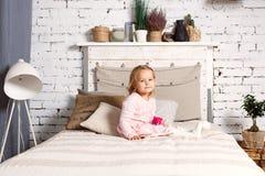 Красивая девушка сидит на кровати Стоковая Фотография
