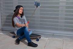 Красивая девушка сидя на скейтборде принимая selfie Стоковые Изображения