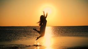 Красивая девушка скача на побережье озера на заходе солнца, Genichesk, u видеоматериал